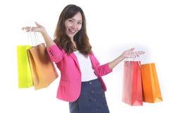 Unga asiatiska kvinnor för shopping som rymmer shoppingpåsar på det vita studiobackgroundSale och befordranbegreppet Arkivbild