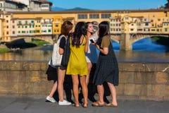 Unga asiatiska kvinnor som tar foto på Ponten Trinita i Florence, Italien Royaltyfri Foto