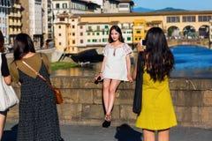 Unga asiatiska kvinnor som tar foto på Ponten Trinita i Florence, Italien Royaltyfri Fotografi