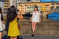 Unga asiatiska kvinnor som tar foto på Ponten Trinita i Florence, Italien Arkivfoton