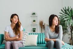 Unga asiatiska lesbiska par argumenterar och vänder deras baksida till varandra i perioden av ledset i sovrummet arkivbild