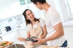 Unga asiatiska man- och kvinnapar som gör tillsammans bagerit att baka ihop och panera arkivbild