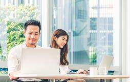 Unga asiatiska par eller högskolestudent som tillsammans använder arbete för anteckningsbok för bärbar datordator på coffee shop  royaltyfri foto