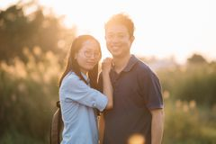 Unga asiatiska par i solsken blossar tycka om solnedgången som kopplar av ha gyckel Royaltyfri Bild