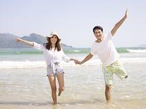 Unga asiatiska par på stranden Arkivbild