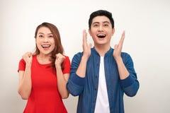 Unga asiatiska par som är förälskade över isolerat fira för bakgrund som förvånas och förbluffas för framgång med lyftta armar oc royaltyfri bild