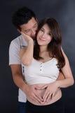 Unga asiatiska par som förväntar, behandla som ett barn Arkivbild