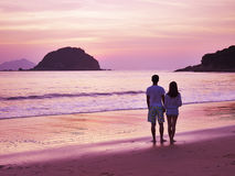 Unga asiatiska par som går på stranden för soluppgång Arkivfoto