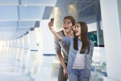 Unga asiatiska par som tar selfie vid smartphonen Arkivfoto