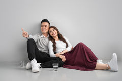 Unga asiatiska par som tillsammans hemma sitter på golv Royaltyfria Foton