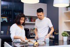 Unga asiatiska par som tillsammans lagar mat, medan kvinnan matar mat Arkivbilder