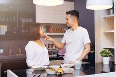 Unga asiatiska par som tillsammans lagar mat, medan kvinnan matar mat till mannen på köket Royaltyfri Bild