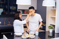 Unga asiatiska par som tillsammans lagar mat, medan kvinnan matar mat till mannen på köket Arkivbild