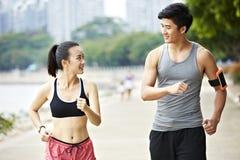 Unga asiatiska par som utomhus joggar Arkivbild