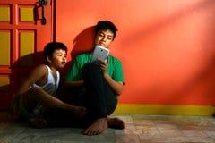 Unga asiatiska ungar, bröder eller syskon, med en minnestavla i en vardagsrum Royaltyfri Foto
