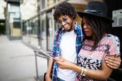 Unga attraktiva afrikanska par som talar och ser den digitala minnestavlan royaltyfria foton