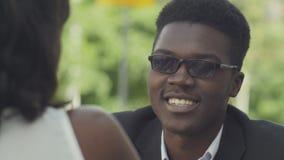Unga attraktiva afro--amerikan affärspar som talar och ler, medan sitta i kafé stock video