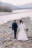 Unga attraktiva brud- par som går på kiselstenen, packar ihop nära bergfloden tillbaka sikt Royaltyfria Foton