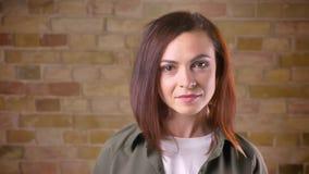 Unga attraktiva brunt-hövdade kvinnavänd till kameran och leenden bricken på väggbakgrund arkivfilmer