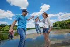 Unga attraktiva föräldrar och barnstående Fotografering för Bildbyråer