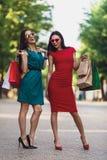 Unga attraktiva flickor med shoppingpåsar i sommarstaden Härliga kvinnor i solglasögon som ser kameran och royaltyfri foto