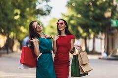 Unga attraktiva flickor med shoppingpåsar i sommarstaden Härliga kvinnor i solglasögon som ser kameran och arkivfoto