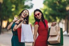 Unga attraktiva flickor med shoppingpåsar i sommarstaden Härliga kvinnor i solglasögon som ser kameran och arkivfoton