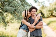 Unga attraktiva hipsterpar som kysser på skogbakgrunden Arkivfoto