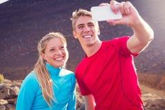 Unga attraktiva idrotts- par som tar fotoet av dem med Royaltyfria Bilder