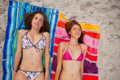 Unga attraktiva kvinnor som solbadar stunder som ta sig en tupplur på stranden Arkivfoto