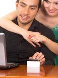 Unga attraktiva lyckliga par framme av datoren Royaltyfri Bild