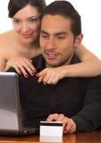 Unga attraktiva lyckliga par framme av datoren Fotografering för Bildbyråer