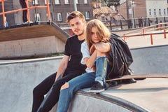 Unga attraktiva par av studenter sitter p? skatepark med deras longboards fotografering för bildbyråer