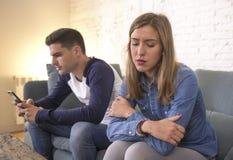 Unga attraktiva par i förhållandeproblem med pojkvännen för internetmobiltelefonböjelse som ignorerar ledsen eftersatt och bekymr arkivfoto