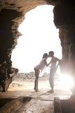 Unga attraktiva par som kysser vaggar igenom, valvgången Royaltyfri Bild