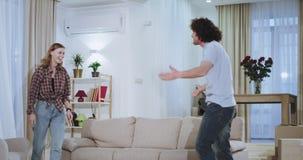 Unga attraktiva par som tycker om tiden i ett nytt hus flyttade de, soffan i mitt av vardagsrum, efter de upphetsas arkivfilmer