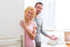 Unga attraktiva par som välkomnar dig i hans hus Royaltyfri Fotografi