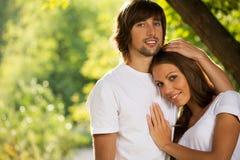 Unga attraktiva par tillsammans utomhus Arkivbild