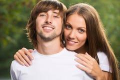 Unga attraktiva par tillsammans utomhus Arkivfoto