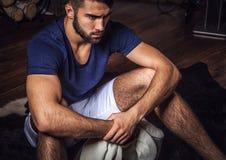 Unga attraktiva skäggiga män i den vita dräkten poserar i modernt rum arkivfoto