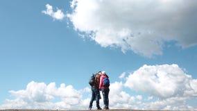 Unga attraktiva turist- par som kysser på bakgrund av fantastisk blå himmel med stora vita moln stock video