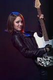 Unga attraktiva vaggar flickan som spelar den elektriska gitarren Arkivfoto