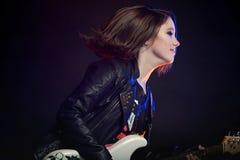 Unga attraktiva vaggar flickan som spelar den elektriska gitarren Arkivfoton