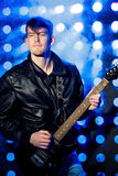 Unga attraktiva vaggar musikern som spelar den elektriska gitarren och att sjunga Vagga stjärnan på bakgrund av strålkastare Arkivbilder