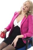 Unga bärande rosa färger för affärskvinna och sitta i en kontorsstol som rymmer en råna Arkivfoton