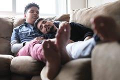 Unga bögar som sover och kopplar av på Sofa At Home royaltyfri foto