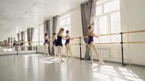 Unga balettdansörer är praktiserande benpositioner på balettstången under vägledning av den strikta läraren för den yrkesmässiga  stock video