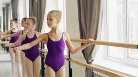Unga ballerina i moderiktiga balettdräkter är praktiserande armförehavanden och plie i ljus danskorridor med träbalett arkivfilmer