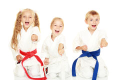 Unga barn med ett leende i kimonosammanträde i en ritual poserar karatestansmaskinarmen Royaltyfri Fotografi