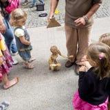 Unga barn ser en trädocka i gatan Arkivbild